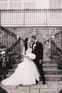 A black and white photo of Alyssa and Rohan kissing on their wedding day