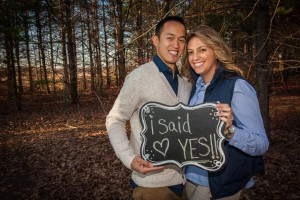 "Tom and Diana in a forest, holding up a sign that reads ""I said yes"""