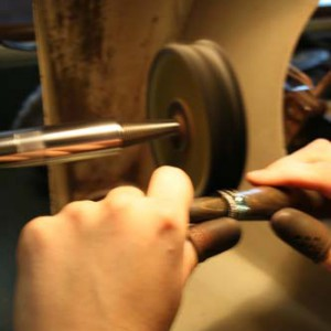 A jeweler holding a ring in front of a polishing wheel.