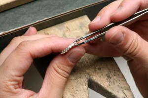 Close up of a jeweler replacing a stone in a diamond wedding band