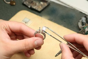 Close up of a jeweler putting a diamond into an engagement ring